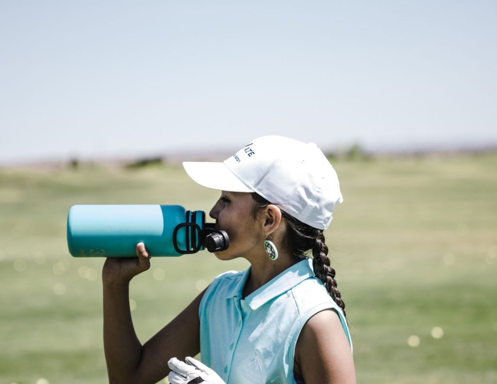 Image of woman in sleeveless polo drinking from a water bottle. Image chosen by Nicole Eva for blog post called The cure why you need more water explaining the benefits of water intake on your health. Health and wellness blogger