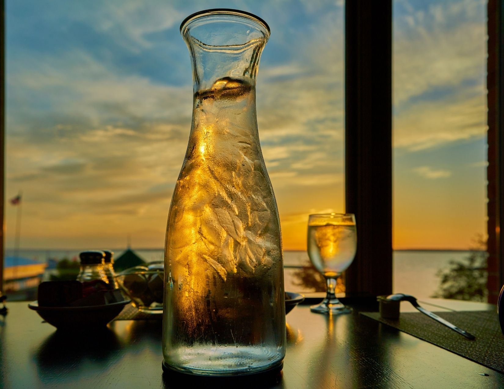 Image of a glass pitcher of water sitting on a table overlooking a sunset
