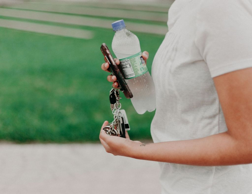 Image of woman in white t shirt holding a phone, keys and a water bottle. Image chosen by Nicole Eva for blog post called The cure why you need more water explaining the benefits of water intake on your health. Health and wellness blogger