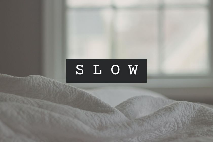 image of crinkled bed sheets header to title of blog post called slow by Nicole Eva highlighting the importance of slow mornings for self care and mental wellness